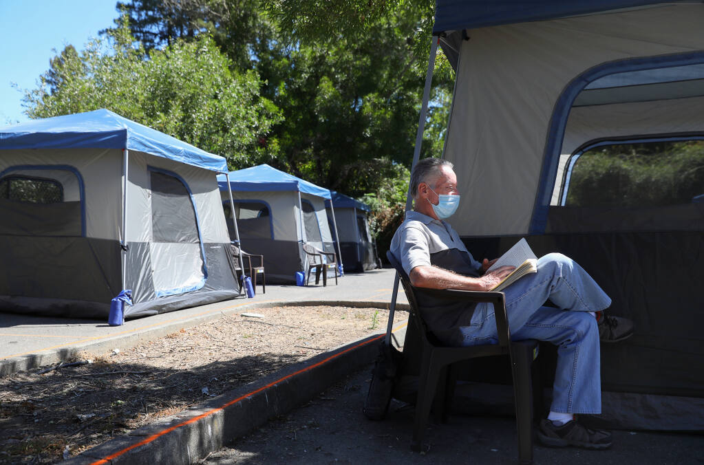 Brian Fielding reads outside of his tent at the newest Sonoma County-provided encampment for homeless individuals in Guerneville on Wednesday, Aug. 12, 2020.  (Christopher Chung / The Press Democrat)