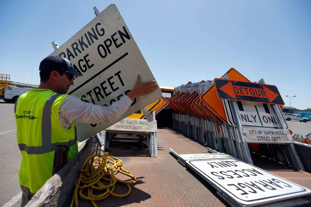 Skilled maintenance worker Alexander Oceguera loads street signs and barricades on the back of a truck at the City of Santa Rosa Municipal Services Center, in preparation for stage 7 of the Amgen Tour of California and Luther Burbank Rose Parade which both occur on Saturday, in Santa Rosa, California on Wednesday, May 18, 2016. (Alvin Jornada / The Press Democrat)