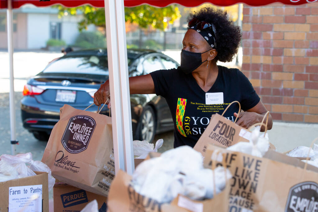 Sonoma County Black Forum board member Claudia de la Pena hands off bags of food to be given to recipients during a food distribution in Santa Rosa on Saturday, Nov. 21, 2020. (Alvin A.H. Jornada / The Press Democrat)