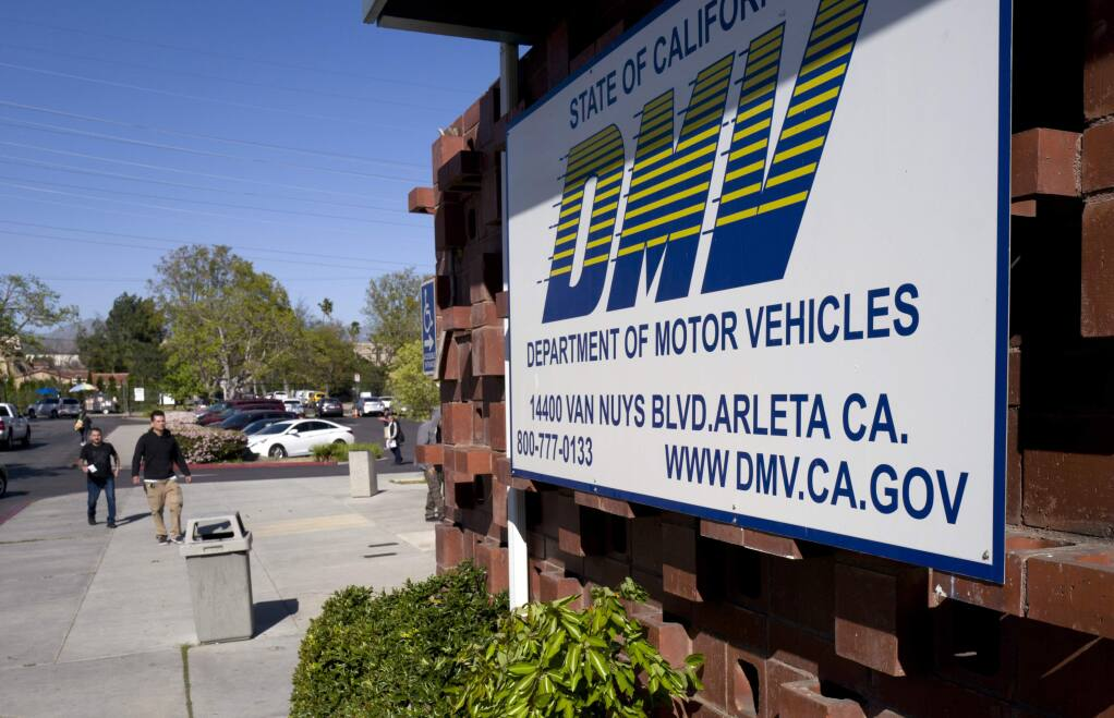 File - In this April 9, 2019, file photo, people approach the California Department of Motor Vehicles office in the Arleta neighborhood of Los Angeles. (AP Photo/Richard Vogel, File)