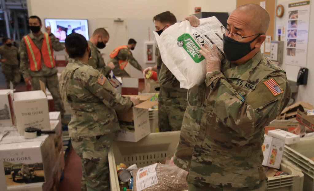 Army National Guard Cpt. Tim Durazzo hefts a large bag of rice as he and other guardsmen sort food at the Redwood Empire Food Bank, Monday, Dec. 28, 2020 in Santa Rosa. (Kent Porter / The Press Democrat) 2020