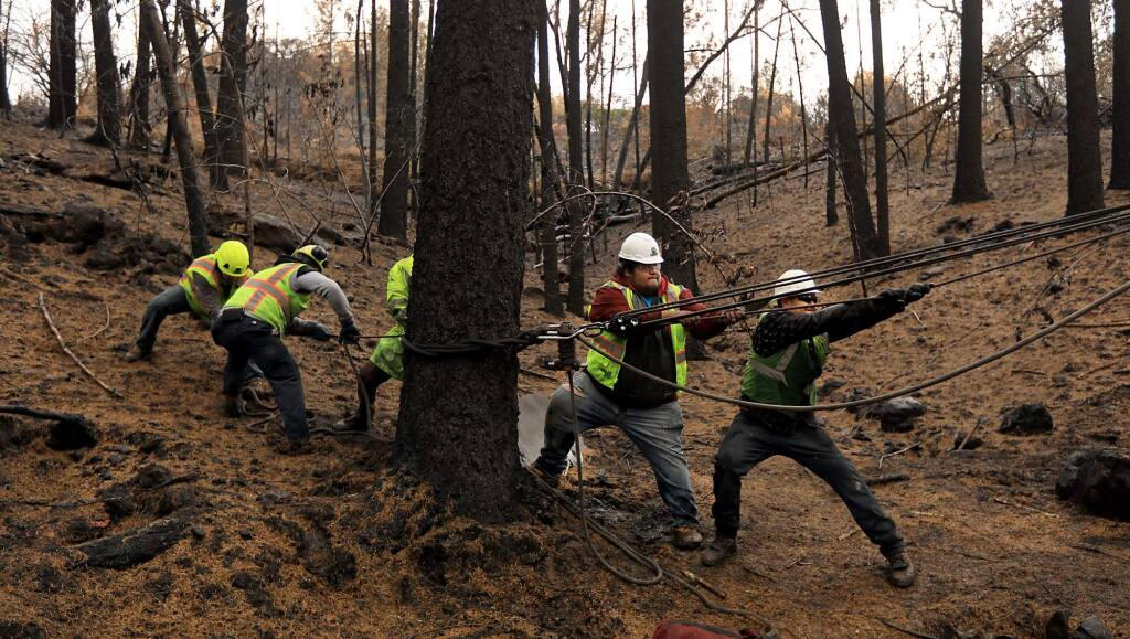A tree removal crew from CORE of Corona, Ca., use a winch system to help take town burned trees on the Matula property in Kenwood, Wednesday Nov. 15, 2017. (Kent Porter / Press Democrat) 2017