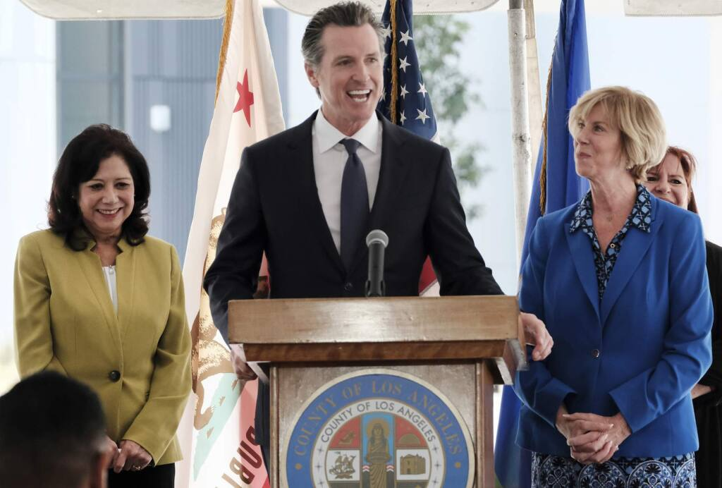 California Gov. Gavin Newsom talks during a news conference while flanked by L.A. County Supervisor Hilda Solis,left and Chair of the Los Angeles County Board of Supervisors Janice Hahn at Rancho Los Amigos National Rehabilitation Center in Downey, Calif. on Wednesday, April 17,2019. (AP Photo/Richard Vogel)
