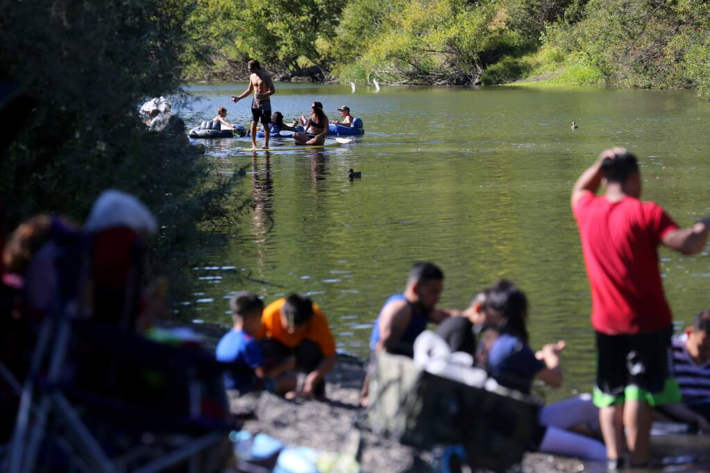 People relax and swim in the Russian River at Steelhead Beach near Forestville on Sunday, Sept. 15, 2019. (Beth Schlanker / The Press Democrat)