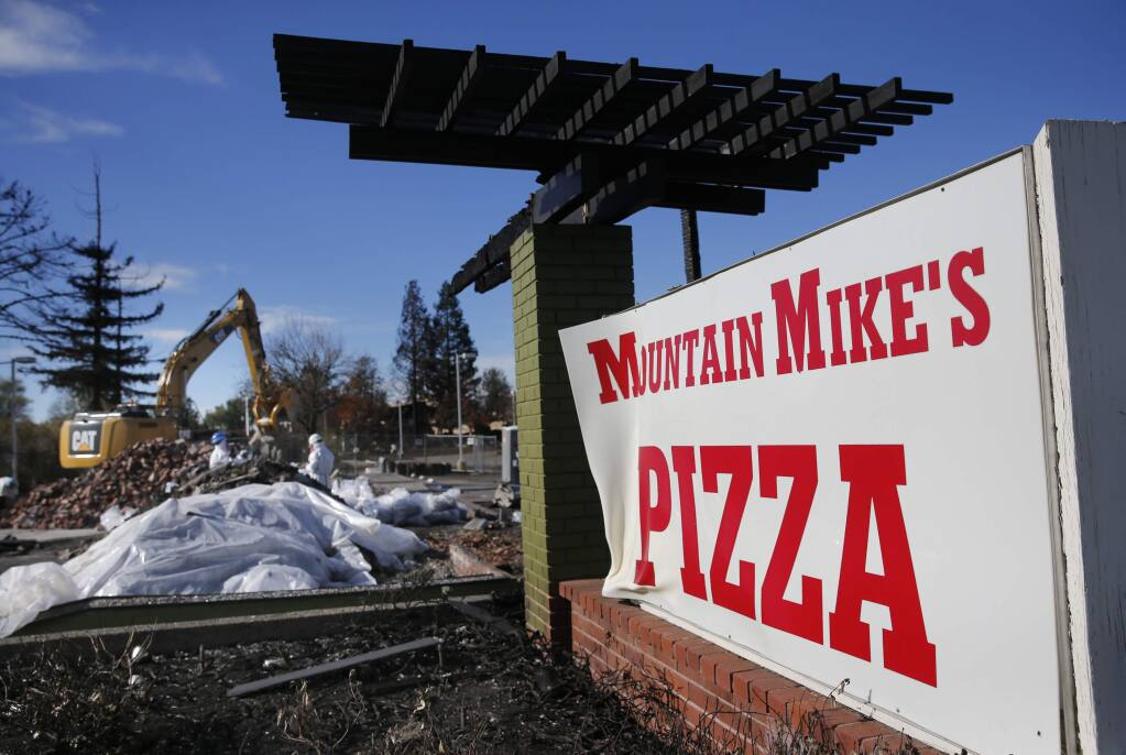Employees of Excel Site Services clean up burned debris at Mountain Mike's Pizza on Cleveland Avenue on Wednesday, Nov. 29, 2017 in Santa Rosa. (BETH SCHLANKER/ PD)