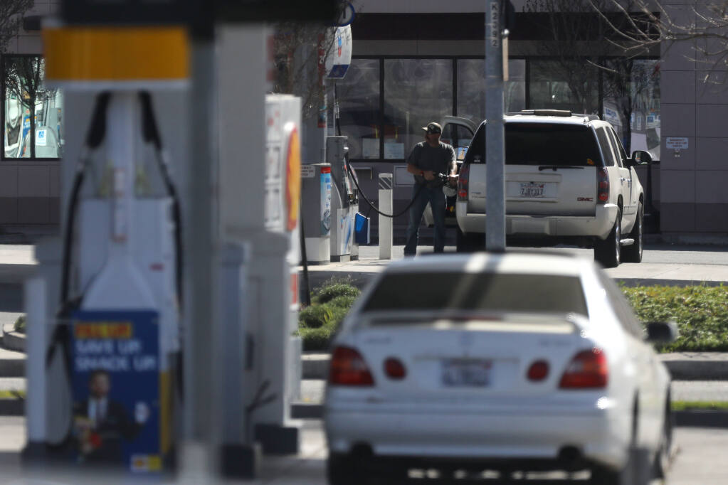 A man fills up his tank at the Chevron gas station located across the street from a Shell gas station at the intersection of Lakeville St. and Caulfield Lanes in Petaluma, Calif., on Thursday, March 4, 2021. (Beth Schlanker/ The Press Democrat)