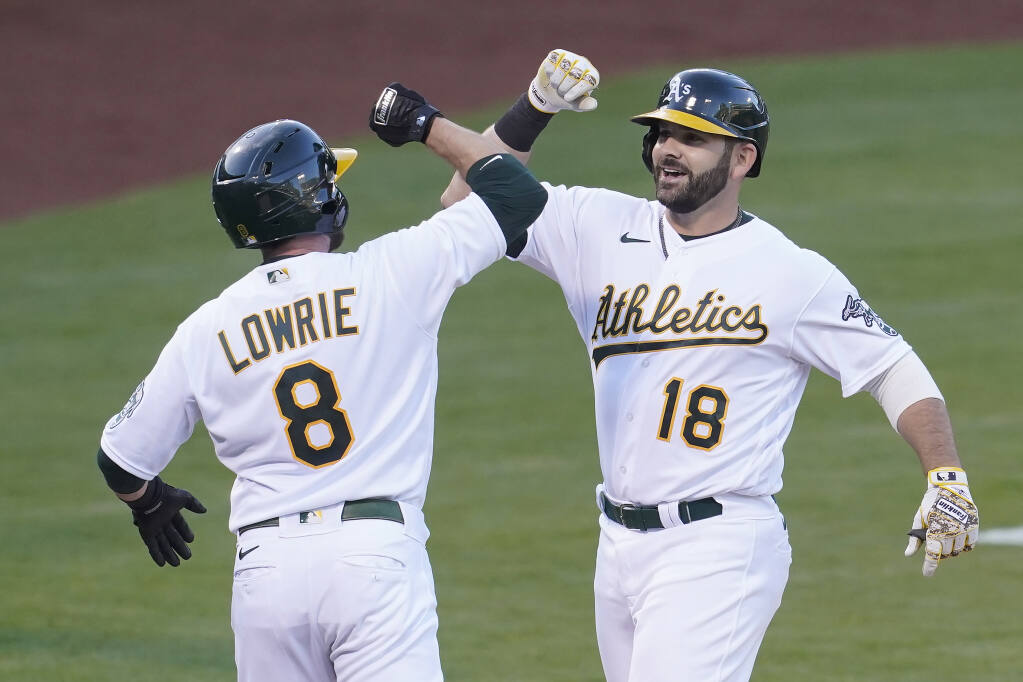 The Oakland Athletics' Mitch Moreland, right, celebrates after hitting a two-run home run that scored Jed Lowrie during the second inning against the Toronto Blue Jays in Oakland on Tuesday, May 4, 2021. (Jeff Chiu / ASSOCIATED PRESS)