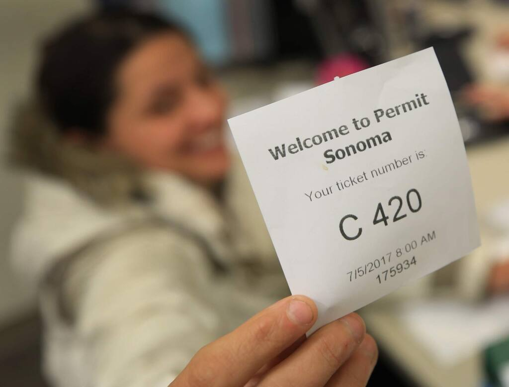 Karen Kohley of Santa Rosa's Flora Cal Farms was the first in line and received the first ticket - 420 - Wednesday July 5, 2017 as she submits her permit for her marijuana business at the Sonoma County Permit and Resource Management Department in Santa Rosa. (Kent Porter / Press Democrat) 2017