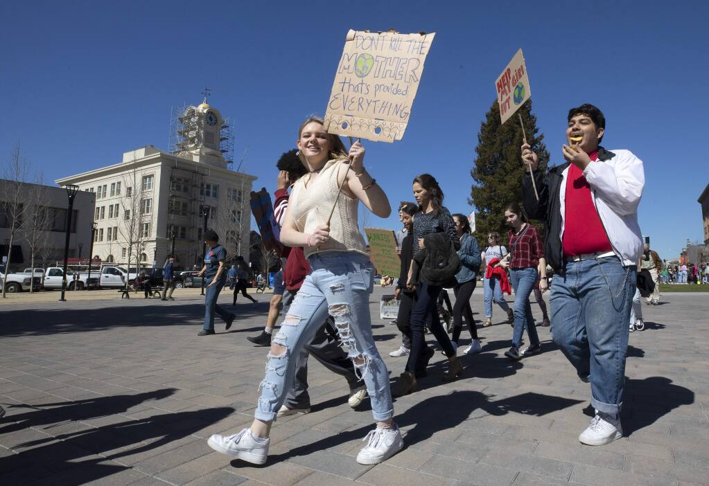 Rancho Cotate sophomores Amanda Knox and Edgar Enriquez, both 16, march down Santa Rosa Avenue to City Hall to demand action against climate change. The rally was a coordinated event with students around the United States and the world. (photo by John Burgess/The Press Democrat)