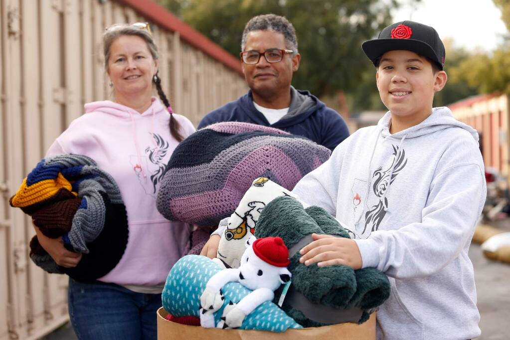 Ian Rich, 13, right, founder of Operation Blanket, which collects new blankets and gives them to homeless families, with his parents Cary and Josiah, in Santa Rosa, California on Saturday, November 25, 2017. The mission of Ian Rich's Operation Blanket has given him and his family a new sense of purpose after their own home was destroyed in the Tubbs Fire. (Alvin Jornada / The Press Democrat)