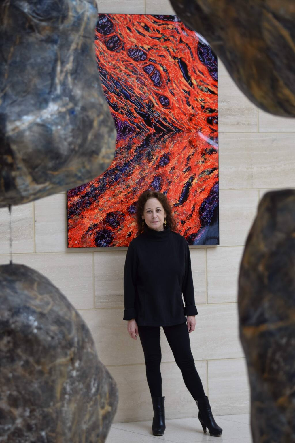 Judy Campisi, Ph.D., co-founder of Novato-based Unity Biotechnology, studies senescent cells and drugs to kill them. The Buck Institute for Age Research art behind her is collagen, enlarged.