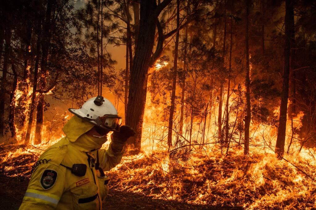 In an effort to create a fire break, volunteer firefighters tend a controlled burn along Princess Highway in Australia's Meroo National Park, Jan. 5, 2020. With thousands fleeing eastern towns this weekend as fires swept from the hills to the coast in Australia, the inescapable realities of a warming world were colliding with the calculated politics of inaction. (Matthew Abbott/The New York Times)