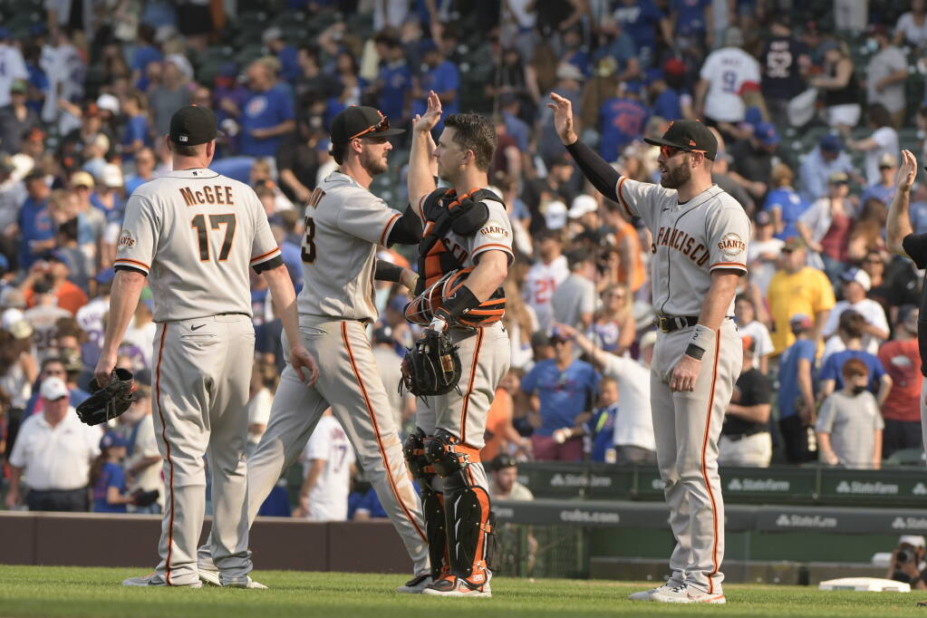 San Francisco Giants players celebrate their win over the Chicago Cubs, Sunday, Sept. 12, 2021, in Chicago. (AP Photo/Mark Black)