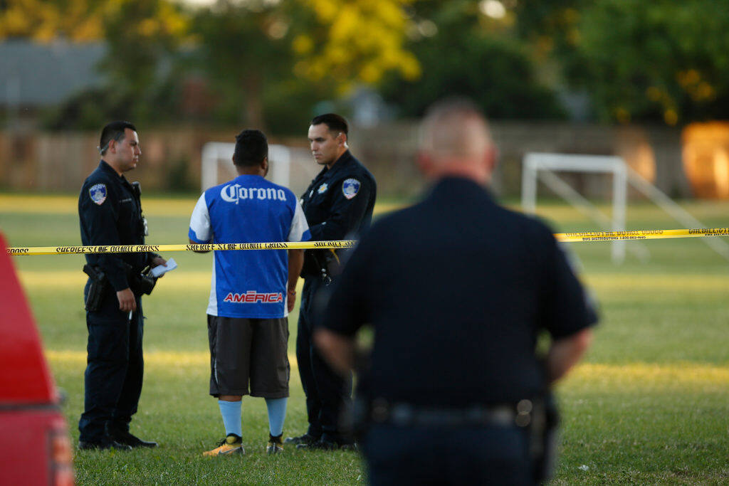 Santa Rosa Police officers interview a witness as they investigate the scene of a shooting at Jacobs Park, in Santa Rosa, California, on Wednesday, June 5, 2019. (Alvin Jornada / The Press Democrat)