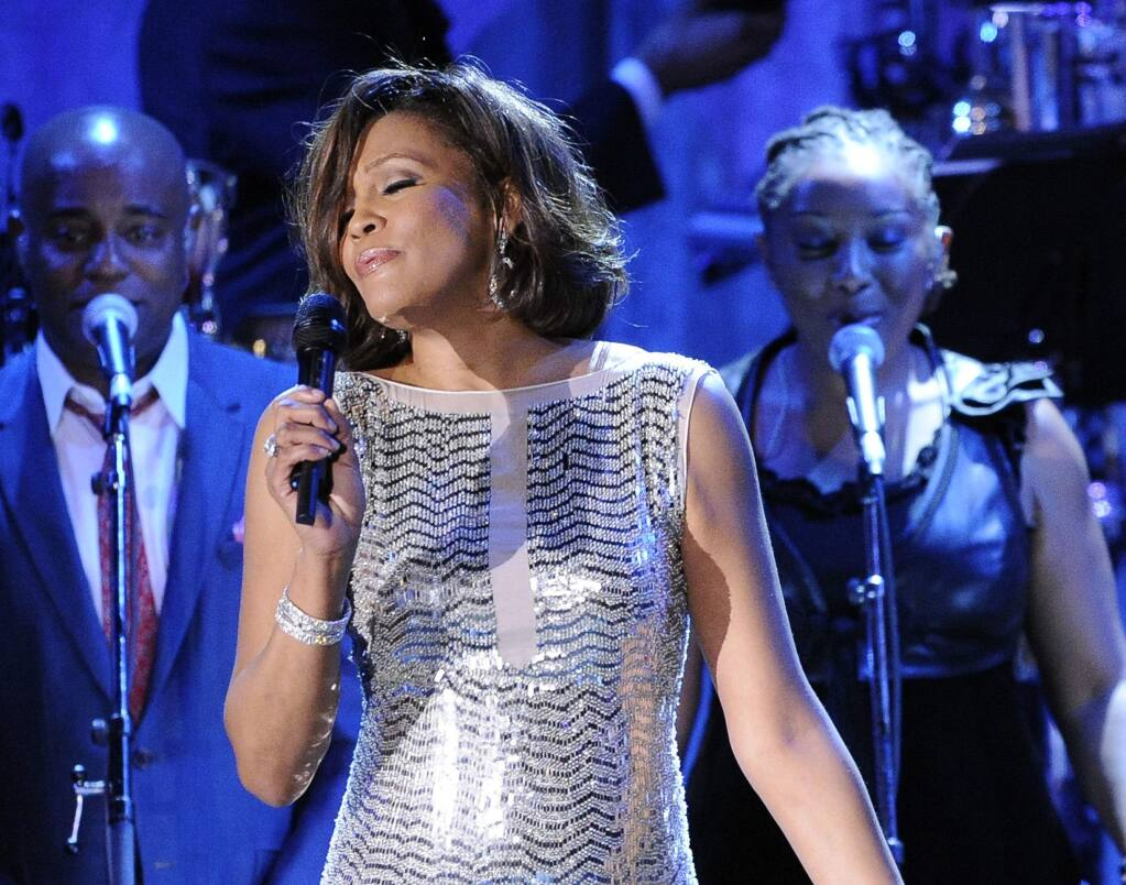 FILE - In this Feb. 13, 2011, file photo, singer Whitney Houston performs at the pre-Grammy gala & salute to industry icons with Clive Davis honoring David Geffen in Beverly Hills, Calif. Friends of Whitney Houston allege the singer was molested as a child by her cousin Dee Dee Warwick in a documentary that premiered Thursday May 17, 2018, at the Cannes Film Festival. (AP Photo/Mark J. Terrill, File)