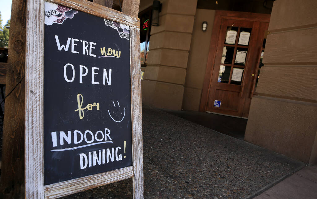 At the Beer Baron Bar and Kitchen on Fourth Street in Santa Rosa, a sign advertises they are open for indoor dining, Wednesday, April  7, 2021. (Kent Porter / The Press Democrat) 2021