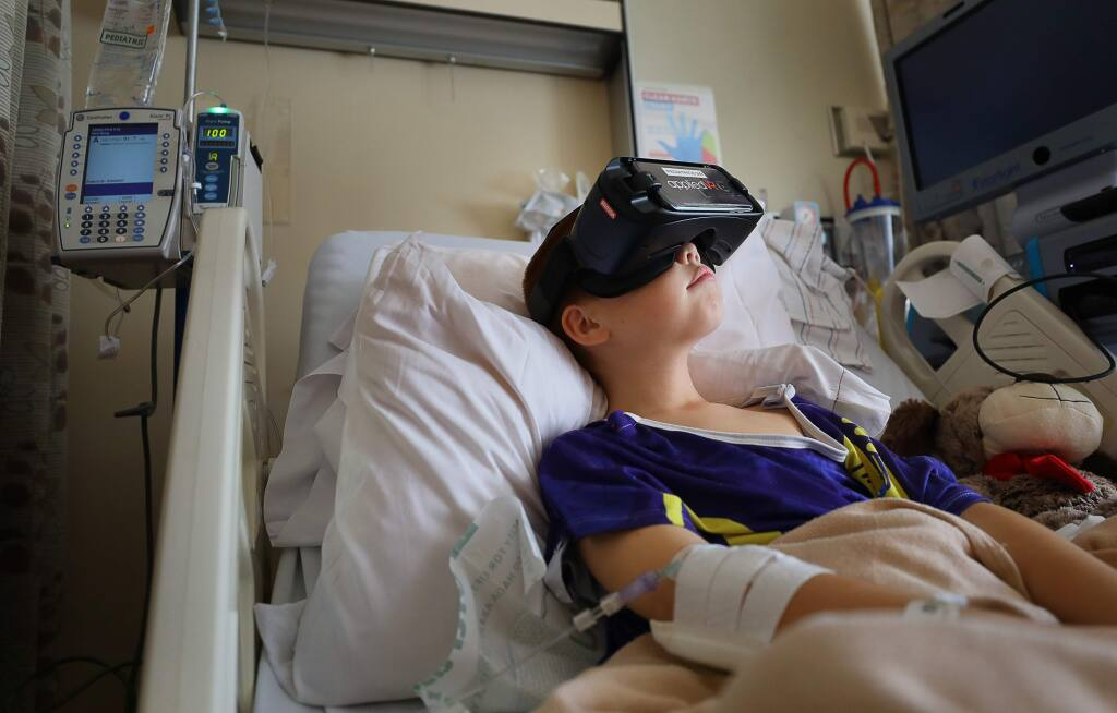 Santa Rosa Memorial Hospital pediatrics patient Andre Slack, 9, relaxes by watching dolphins swim in a virtual reality headset on Friday, August 9, 2019. (Christopher Chung/ The Press Democrat)