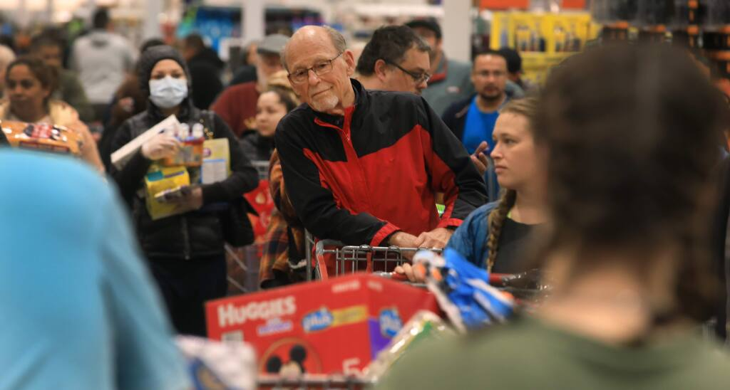 Customers wait in long lines to buy their goods at the Costco store in Santa Rosa, Friday, March 13, 2020.(Kent Porter / The Press Democrat) 2020
