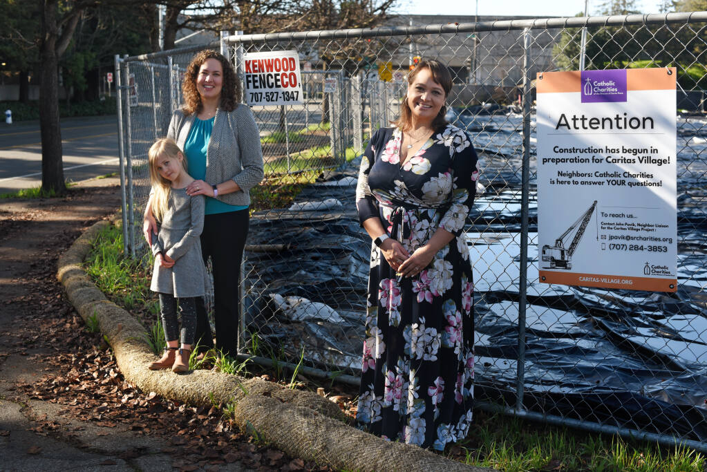 Chief Development Officer Rebecca Kendall, left, with her daughter, Lily Kendall, 5, and Chief Program Office Jennielynn Holmes of Catholic Charities of the Diocese of Santa Rosa at the location of Caritas Village, which will provide shelter and services to homeless people in downtown Santa Rosa, on Saturday, Jan. 16, 2021. Plans are for the site to be operating by summer 2022.(Erik Castro / For The Press Democrat)