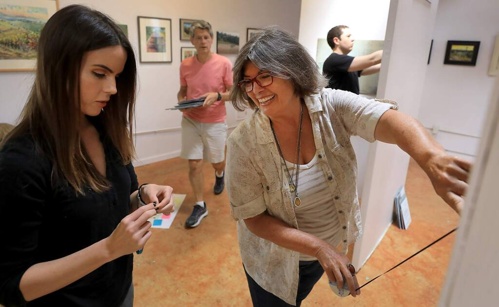 Sonoma State University anthropologist Dr. Margaret Purser, right and SSU student Hannah Bowman of Santa Rosa, hang an exhibit 'Highway 101 in the Neighborhood' at the Santa Rosa Arts Center on South A Street. Purser is leading the creation of an online Santa Rosa Neighborhood Heritage Mapping Project, Friday, July 13, 2018. (Kent Porter / The Press Democrat) 2018