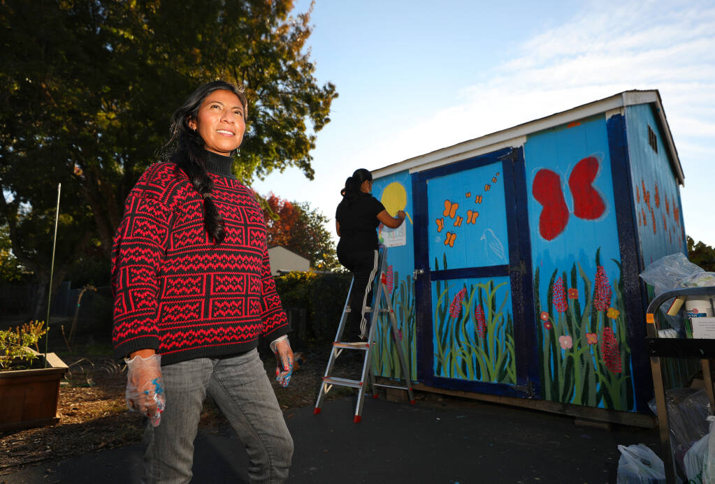 Isabel Lopez, founder and executive director of Raizes Collective, is overseeing the painting of a garden shed mural at La Plaza at Abraham Lincoln Elementary School in Santa Rosa.  (Christopher Chung / The Press Democrat)