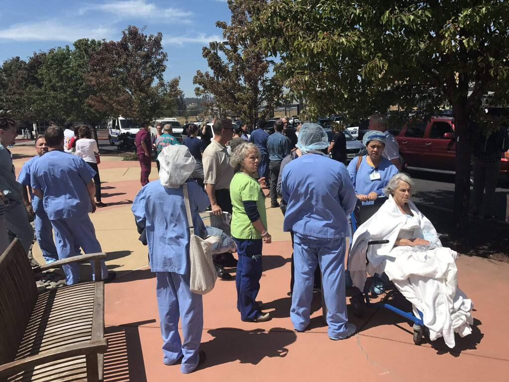 Staff members and patients were outside the Kaiser Permanente medical office building north of Santa Rosa on Old Redwood Highway on Wednesday, July 18, 2018, where a truck crash caused a reported explosion and fire, triggering an evacuation and the closure of nearby Highway 101. (BETH SCHLANKER/ PD)