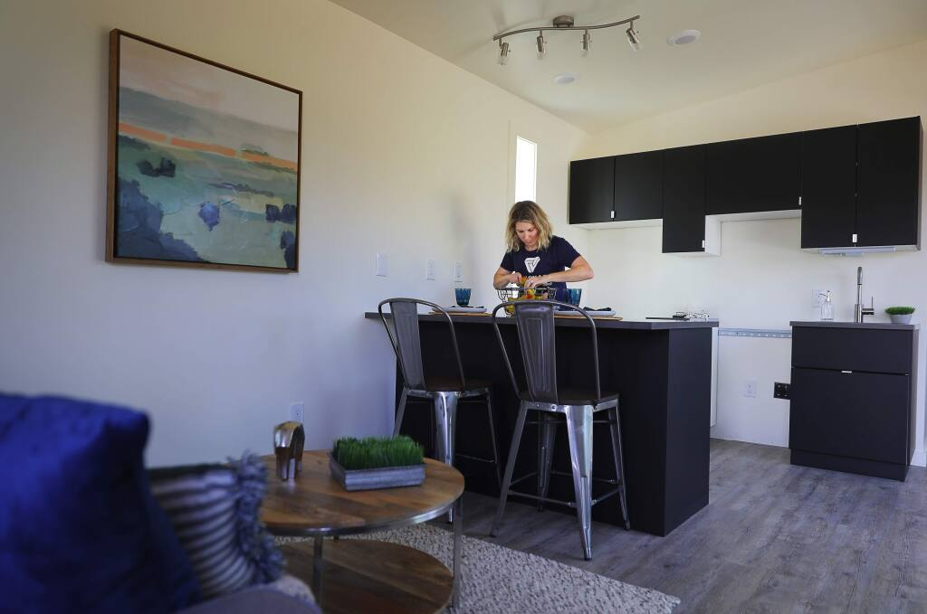 Shannon Howard-Bisordi, with Vanguard Properties, decorates the kitchen of a cottage for Homes for Sonoma, in Fulton on Wednesday, October 3, 2018. The goal of Homes for Sonoma is to create cost-effective neighborhoods for individuals and families displaced by the fires, and those being squeezed out of the rental housing market in Sonoma County.(Christopher Chung/ The Press Democrat)
