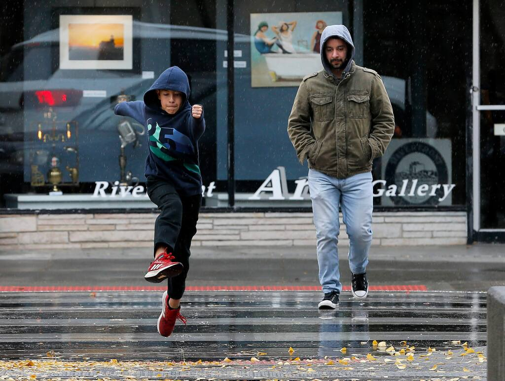 Chris Newton III, 9, leaps over a puddle while crossing Petaluma Boulevard with his father, Chris Newton Jr., during a rainy day in Petaluma, California, on Tuesday, Nov. 26, 2019. (ALVIN JORNADA/ PD)