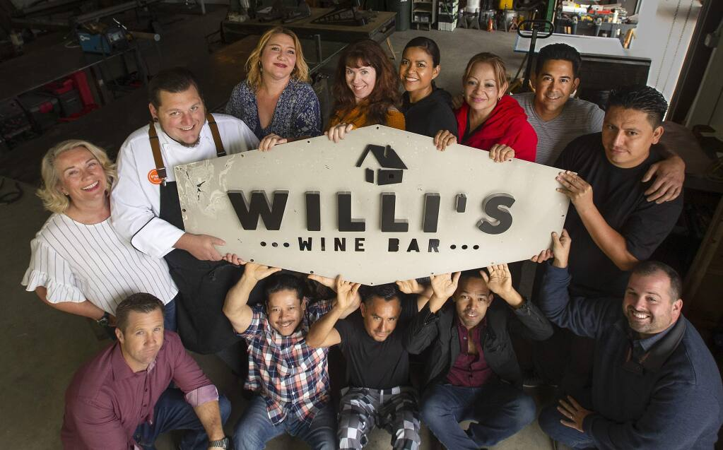 Former employees of Willi's Wine Bar hold the old burnt sign being readied to install in the new location in the Town and Country Shopping Center in northeast Santa Rosa. The crew presently work for other Stark's restaurants until the new location opens. (photo by John Burgess/The Press Democrat) Sept. 20, 2018