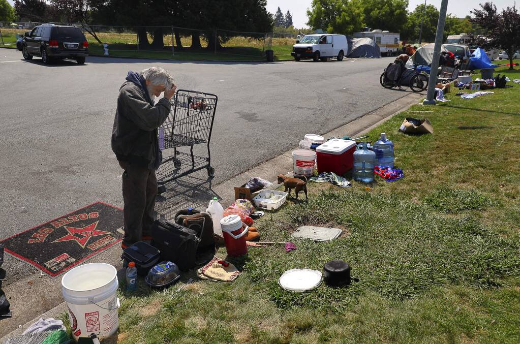 Albert Bruin works on gathering his belongings after the van that he was living in was towed from Challenger Way, in Santa Rosa on Monday, August 13, 2018. (Christopher Chung/ The Press Democrat)