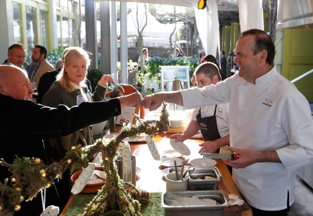 Chef Charlie Palmer, right, serves guests at the 2018 Pigs & Pinot benefit at Hotel Healdsburg. This spring, the chef is offering a virtual Pigs & Pinot cooking class series. (Alvin A.H. Jornada / The Press Democrat)