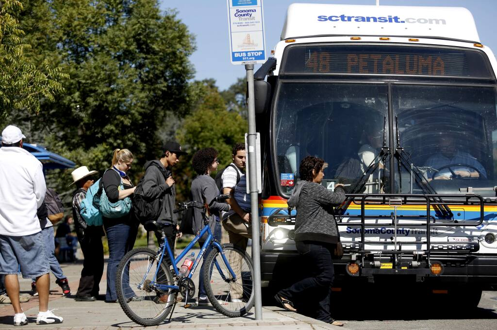 People line up for a Sonoma County Transit bus toward Petaluma at the bus stop on Mendocino Ave. at Pacific Ave. in Santa Rosa, California on Tuesday, September 30, 2014. (BETH SCHLANKER/ The Press Democrat)