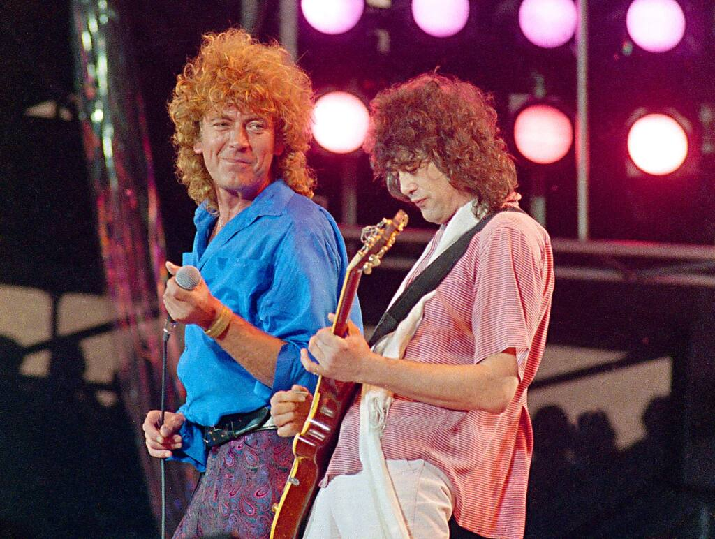 In this July 13, 1985 file photo, Led Zeppelin bandmates, singer Robert Plant, left, and guitarist Jimmy Page, reunite to perform for the Live Aid famine relief concert at JFK Stadium in Philadelphia. (AP Photo/Amy Sancetta, File)
