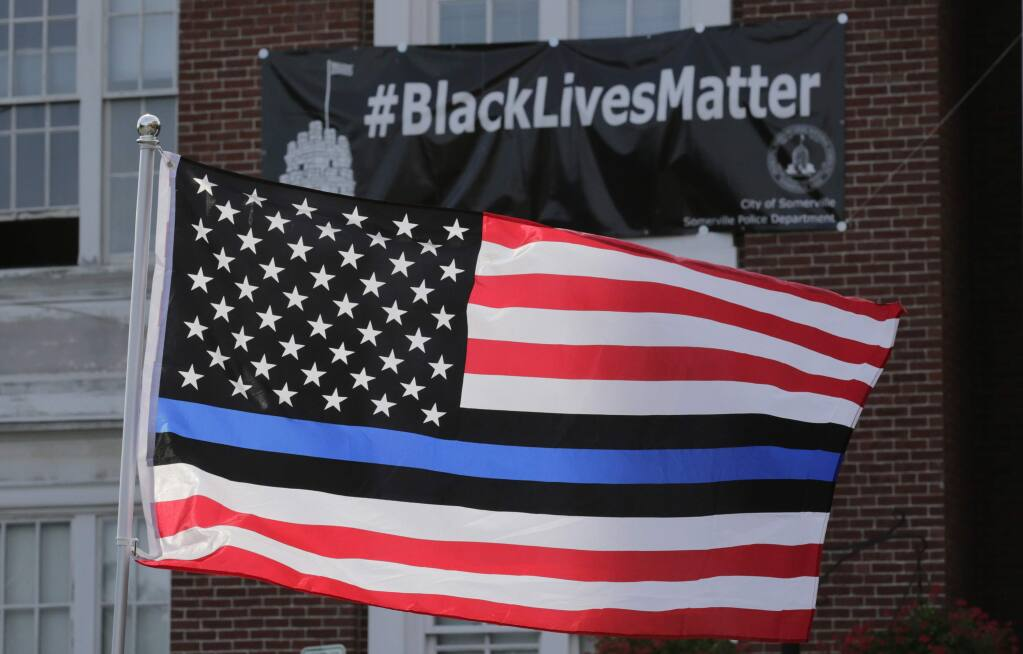 A flag with blue and black stripes in support of law enforcement officers, flies at a protest by police and their supporters outside Somerville City Hall in Somerville, Massachusetts.The Santa Rosa Police Department recently posted a banner on social media that included such a flag, then deleted the post after community objections.  (Charles Krupa / Associated Press, 2016)
