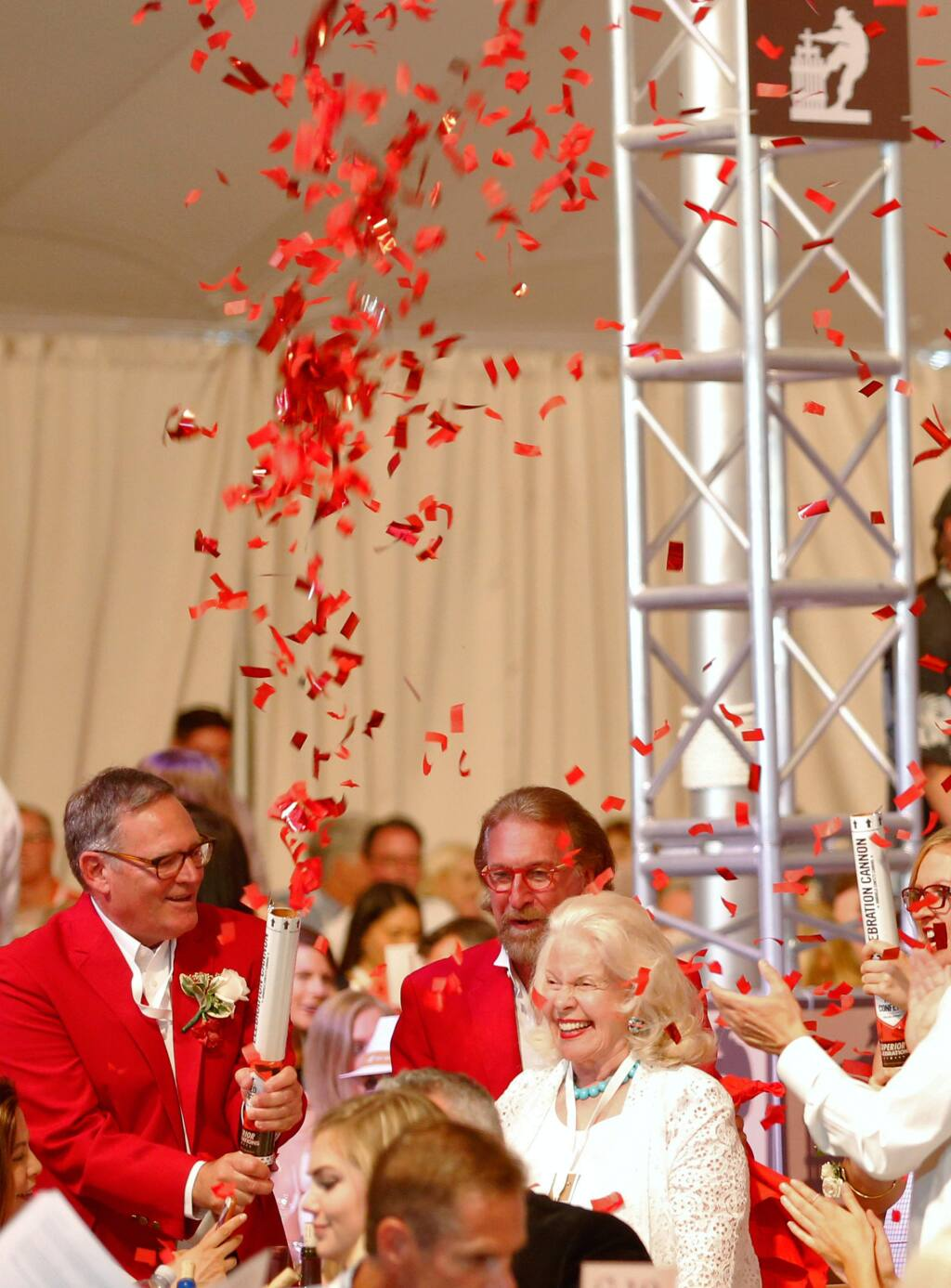 Michael Silacci, left, co-chair of the Hoopla Committee and winemaker at Opus One, shoots confetti in the air to celebrate with a winning bidder during Auction Napa Valley at Meadowood in St. Helena, California on Saturday, June 4, 2016. (Alvin Jornada / The Press Democrat)