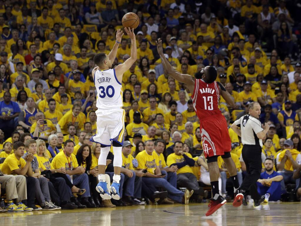 Golden State Warriors' Stephen Curry (30) makes a 3-point basket over Houston Rockets' James Harden (13) during the first half in Game 1 of a first-round NBA basketball playoff series Saturday, April 16, 2016, in Oakland, Calif. (AP Photo/Marcio Jose Sanchez)