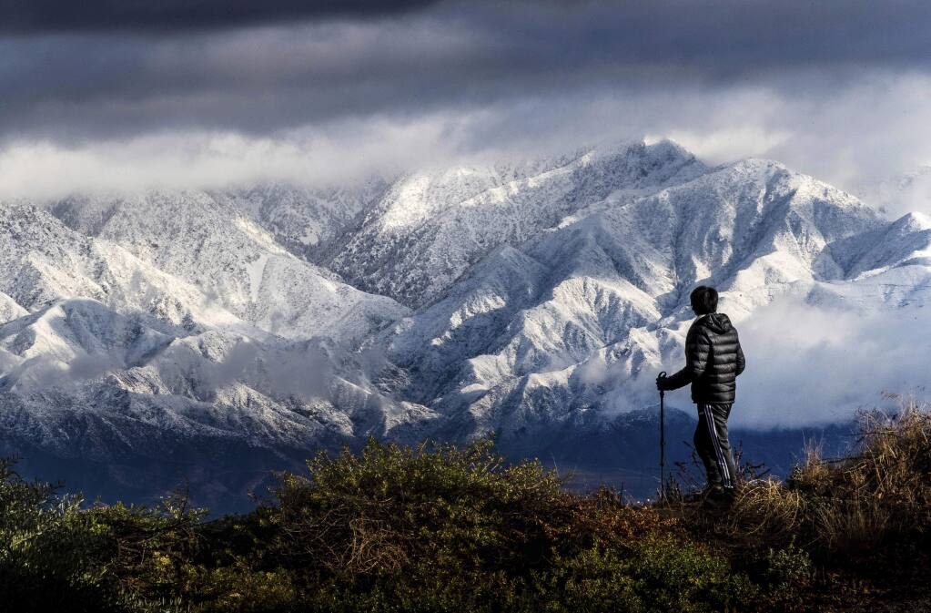 Frank Huong takes a break from hiking to enjoy a view of snow-capped San Gabriel Mountains from Hidden Hills trail in Chino Hills, Calif., on Friday, Nov. 29, 2019. Rain and snow showers are continuing in parts of the state Friday morning while skies are clearing elsewhere. ( Watchara Phomicinda/The Orange County Register via AP)