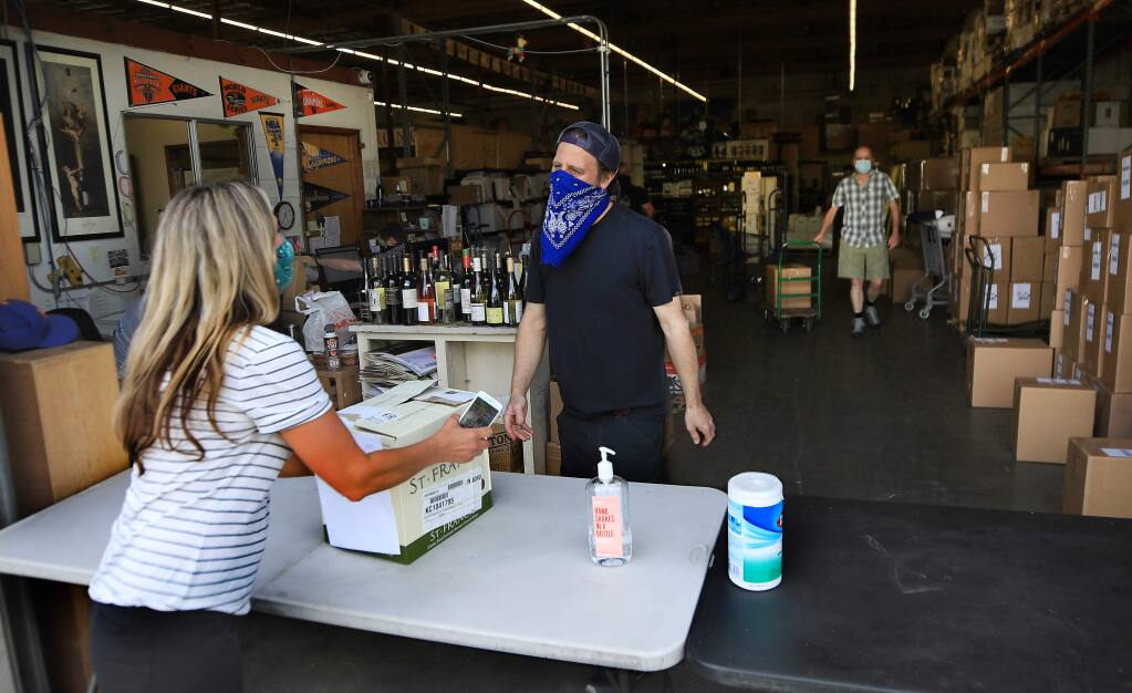 Diana Fox of Santa Rosa picks up her pre-ordered wine from Bottle Barn store manager Jason Schneider during Sonoma County's first day for curbside purchases for a variety of businesses Friday, May 8, 2020, in Santa Rosa. (Kent Porter / The Press Democrat) 2020