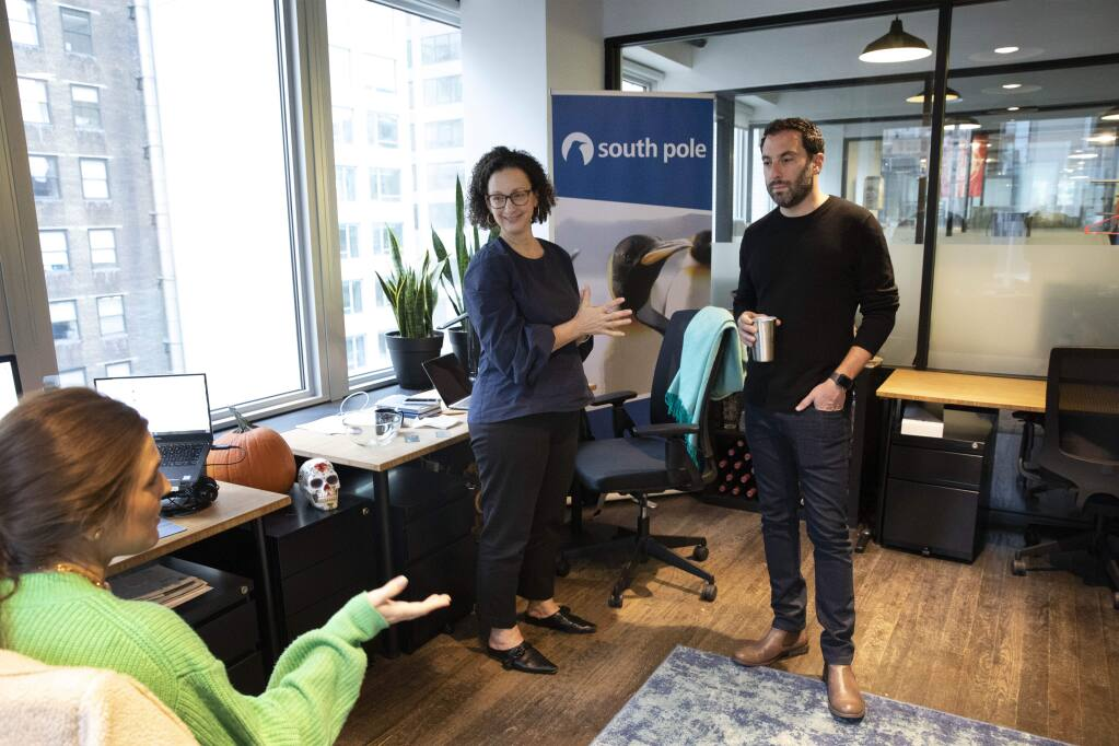In this Tuesday, Nov. 5, 2019 photo, Erin Horleman, left, and Anne-Marie McGonnigal, with South Pole, meet with Lanny Grossman, owner of public relations firm EM50 Communications, at a WeWork office space in New York. WeWork is slashing the lavish spending that has fueled its breakneck growth while racking up unsustainable losses. Experts are skeptical that the office-sharing company can achieve meaningful cost reductions without somehow squeezing tenants. (AP Photo/Mark Lennihan)