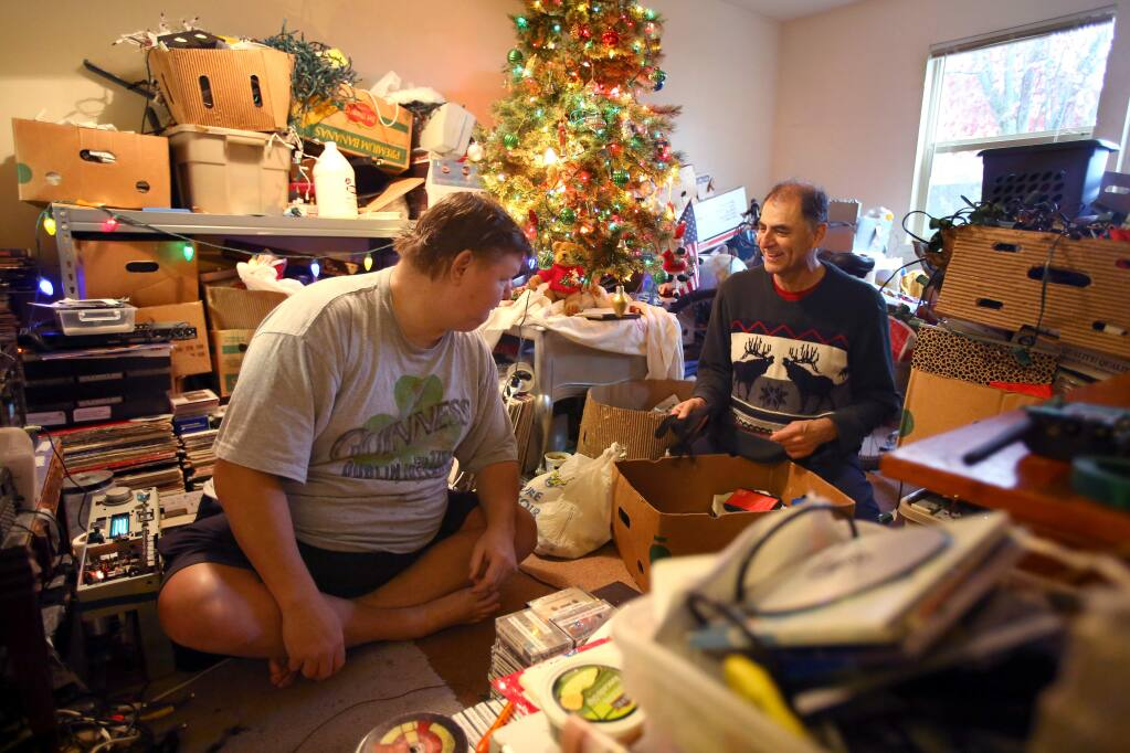 In-home caregiver Paul Esparza, right, negotiates what can be thrown out with his client, Jason Carlin, at Carlin's apartment in Rohnert Park on Friday, December 19, 2014. (Christopher Chung/ The Press Democrat)