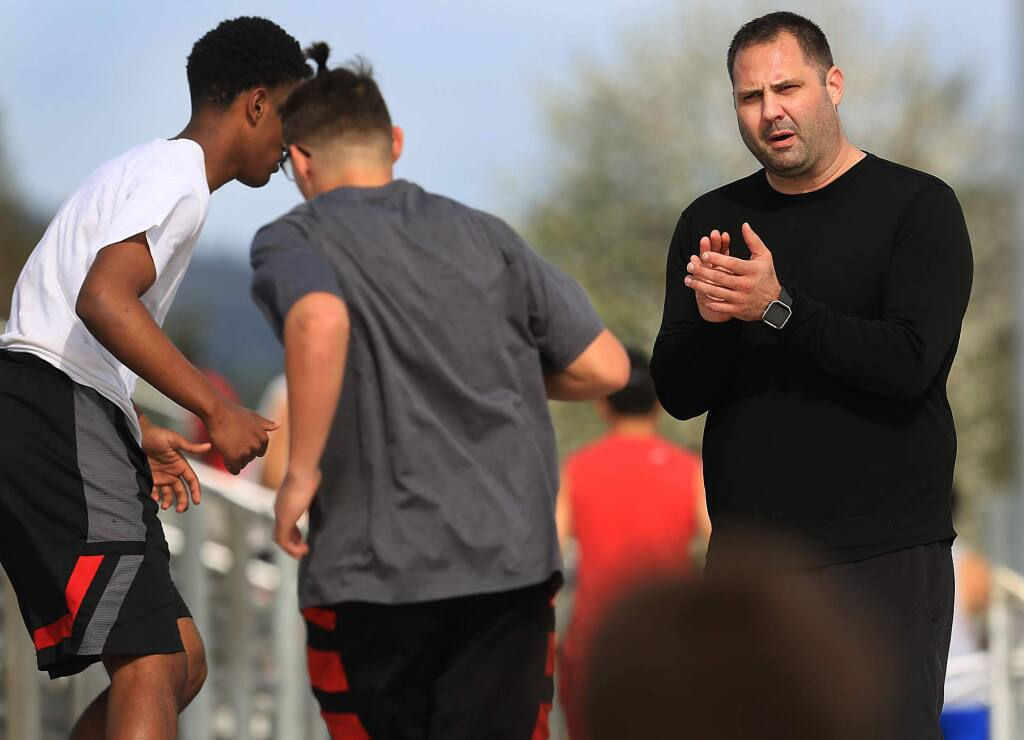 Montgomery High School head football coach Tony Keefer, cheers on his players as they run Montgomery's stadium stairs during spring conditioning, Thursday March 16, 2017 in Santa Rosa. (Kent Porter / The Press Democrat)
