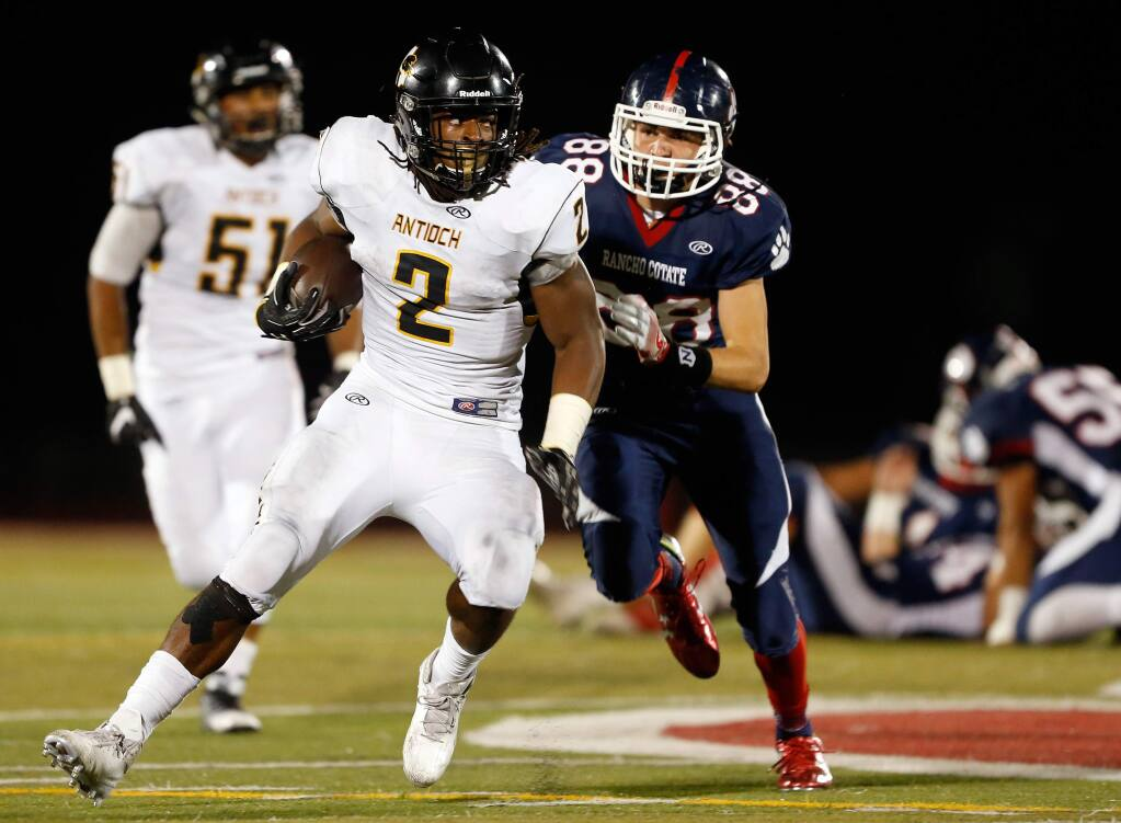 Antioch's Najee Harris (2) carries the ball while pursued by Rancho Cotate's Connor Barbato (88) during the first half of a varsity football game between Antioch and Rancho Cotate high schools, in Rohnert Park, California on Friday, September 16, 2016. (Alvin Jornada / The Press Democrat)