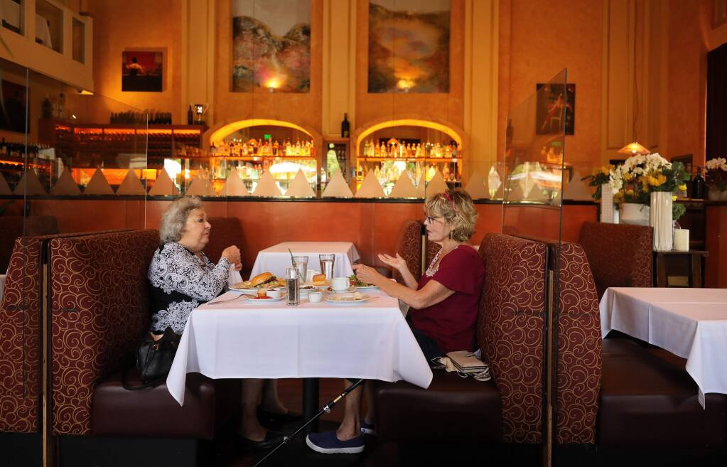 Arlene Rowe, left, and Collette Stricker enjoy lunch at Ristorante Allegria, in Napa on Friday, May 29. Though the restaurant installed clear plastic barriers between tables in their indoor dining area, it was ordered to close indoor dining on July 13 along with all California restaurants because of rising coronavirus numbers. (Christopher Chung/ The Press Democrat)