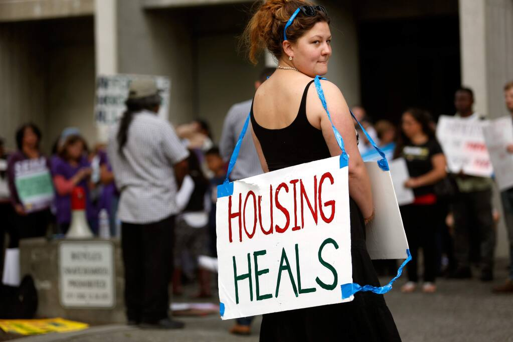 Eva Granahan carries a sign in support of affordable housing with a group of demonstrators outside the Santa Rosa city council chambers before a meeting to discuss rent control in Santa Rosa, California on Tuesday, May 3, 2016. (Alvin Jornada / The Press Democrat)