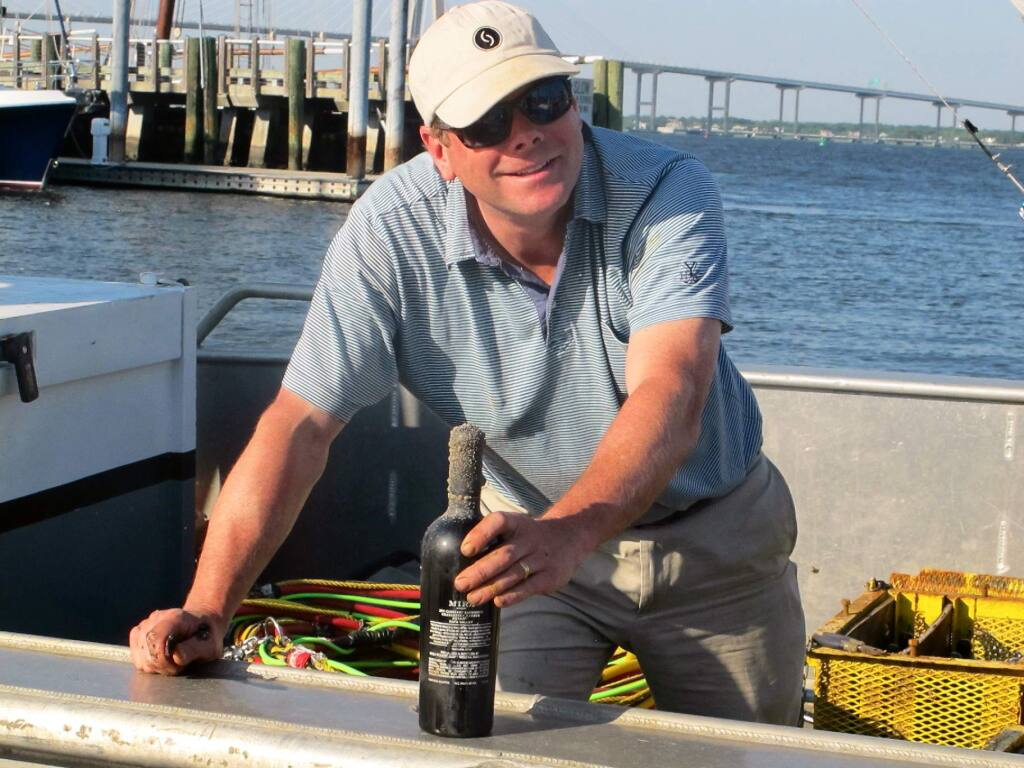 Jim 'Bear' Dyke, the owner of Mira Winery, hands a bottle of wine off a boat docked in Charleston, S.C., on Tuesday, May 6, 2014. The wine had just been recovered after being aged in Charleston Harbor for six months as part of an ongoing experiment by the winery to gauge the effect of ocean aging on wine. Other cases of wine had been aged in the harbor last year for three months. (AP Photo/Bruce Smith)