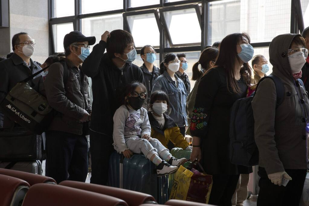Travelers wearing face masks to help curb the spread of the coronavirus line up for their train at the station in Beijing on Sunday, March 29, 2020. As the coronavirus epicenter has shifted westward, the situation has calmed in China, with falling death rates and most new cases coming from abroad, restrictions on travel have been slowly lifted. (AP Photo/Ng Han Guan)