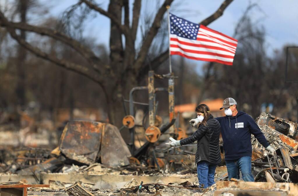 Linda and Jason Miller spot an item of interest in the burned home in Coffey Park, Friday Oct. 20, 2017 in Santa Rosa. (Kent Porter / Press Democrat) 2017