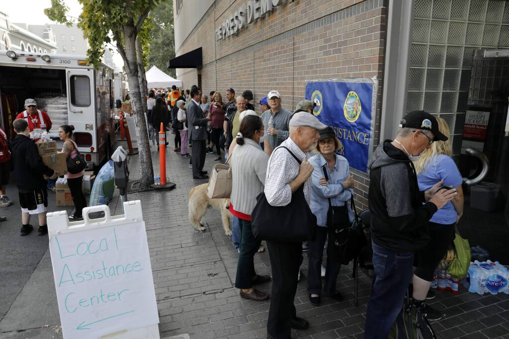 People line up outside the FEMA hub at 427 Mendocino Ave in Santa Rosa, on Monday, October 16, 2017. (BETH SCHLANKER/ The Press Democrat)