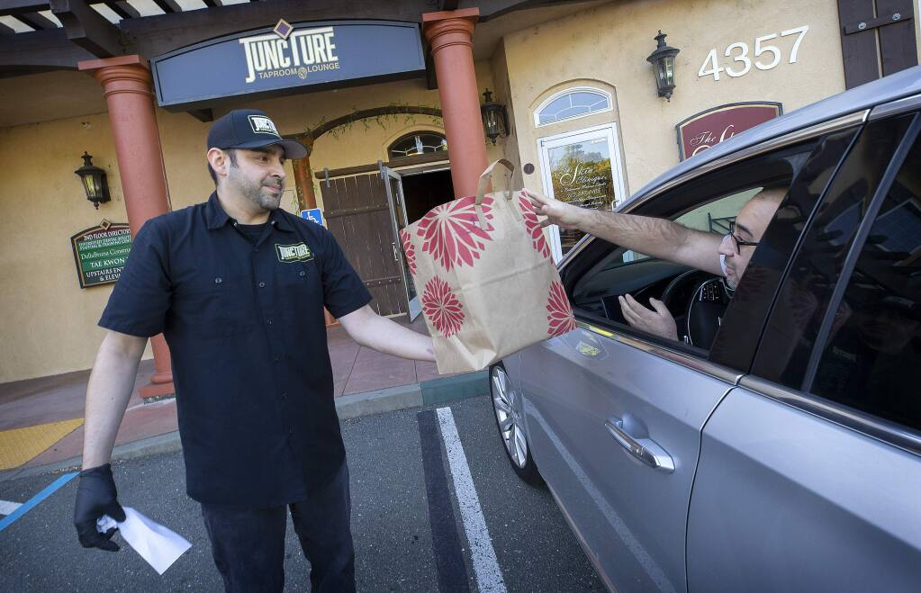 Peter Lopez Jr., owner of Juncture Taproom & Lounge, delivers a to-go food order and a growler of beer to David Magallon outside of his Santa Rosa restaurant on Wednesday, April 1, 2020. (John Burgess/The Press Democrat)