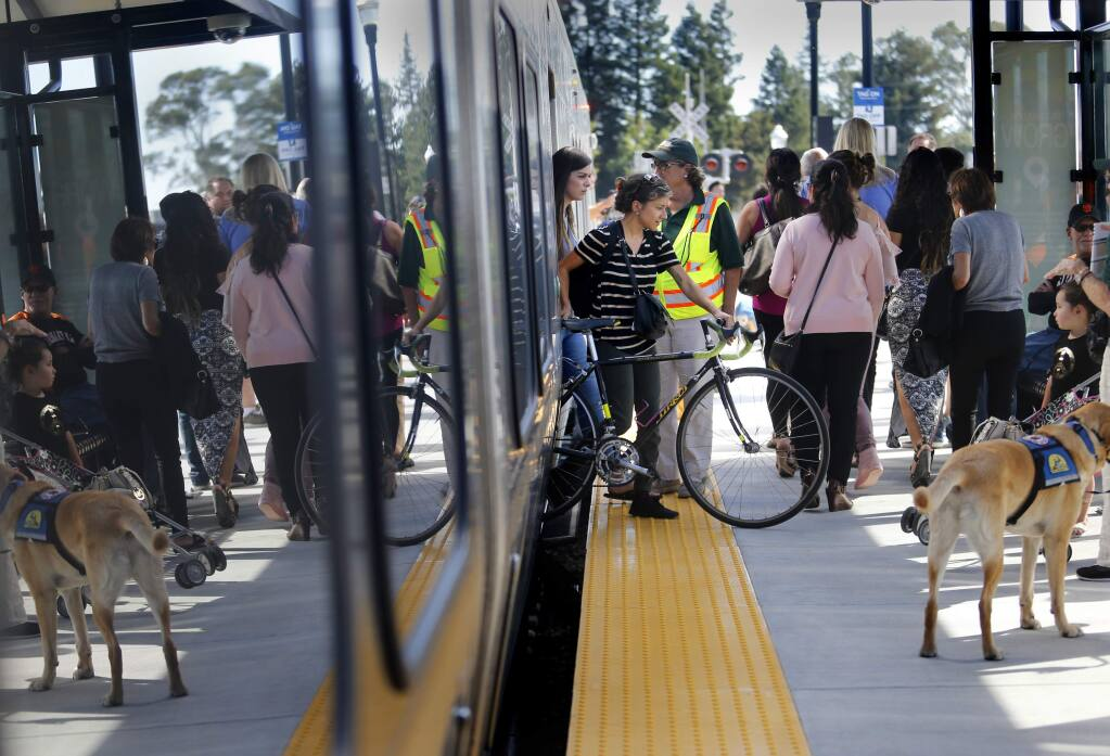 Lupita C.A. maneuvers her bicycle as she disembarks from the SMART train on Friday, Sept. 29, 2017 in Santa Rosa, California. (BETH SCHLANKER/ PD)